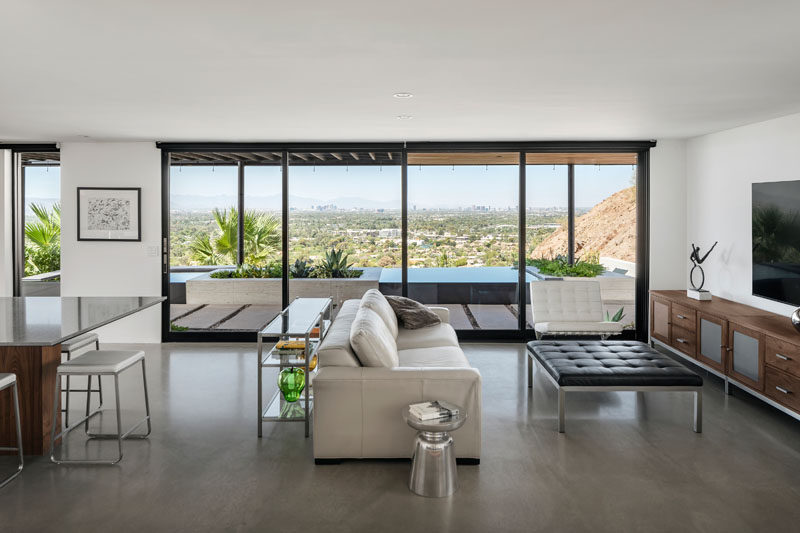 Inside this modern house, floor-to-ceiling windows and sliding glass doors frame the desert view from the living room and kitchen. #Windows #InteriorDesign #ConcreteFloors