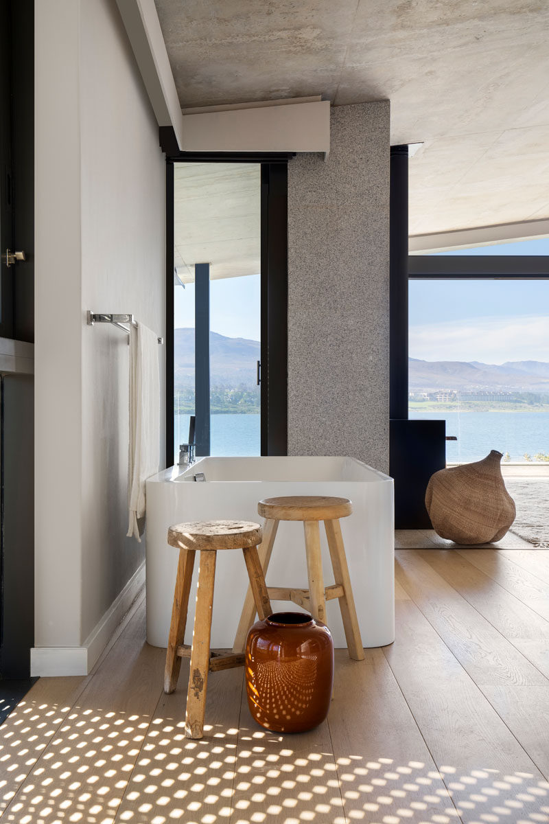 In this modern bathroom that's open to the bedroom, wood flooring adds warms to the space, while a vertical window provides a glimpse of the view from the bathtub. #ModernBathroom #FreestandingBathtub