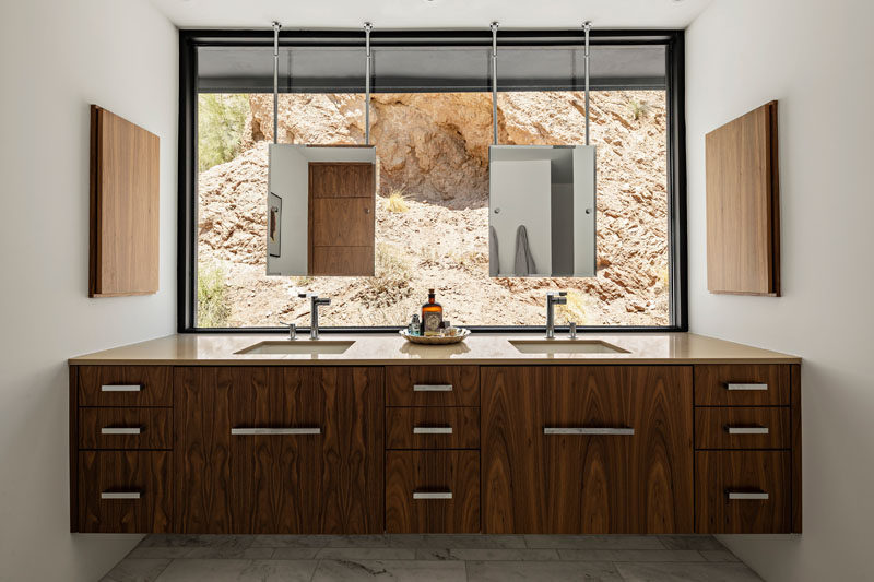 In this master bathroom, a large window allows the rocks to become the backdrop for the mirrors. #MasterBathroom #BathroomVanity #Windows