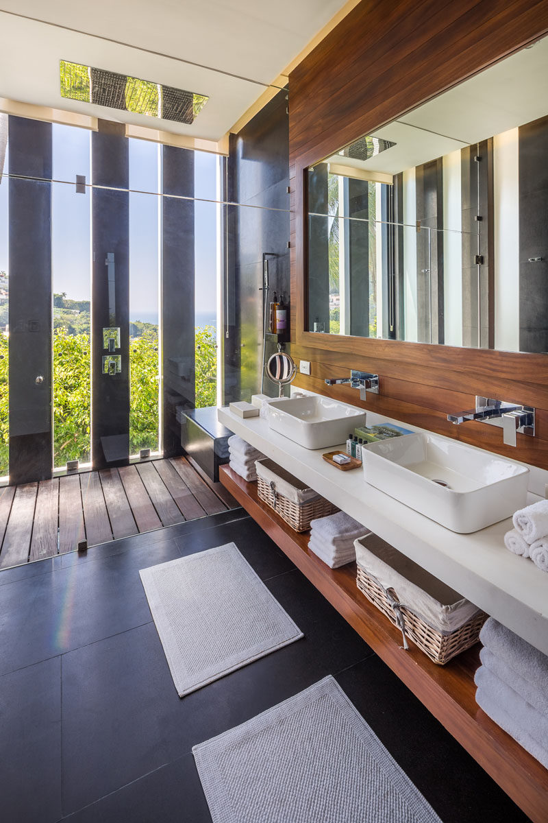 In this modern bathroom, floor to ceiling glass separates the shower from the vanity, while narrow vertical windows give a glimpse of the tree view outside. #MasterBathroom #DualVanity #BathroomDesign #ModernBathroom