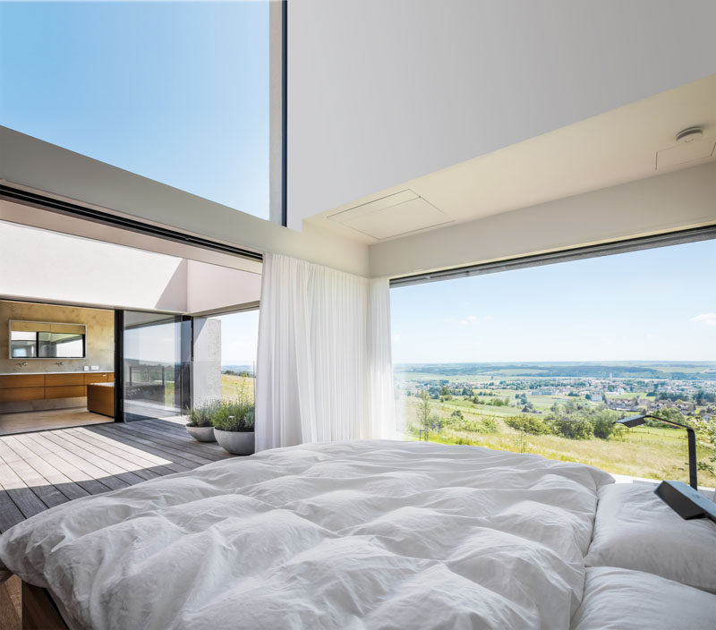 This modern master suite has the master bath and bedroom face and open up to a secluded open-air atrium. #MasterBedroom #MasterSuite #MasterBathroom #Archtiecture