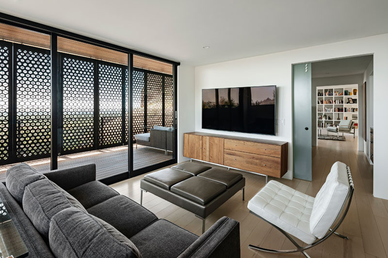 This modern living room opens up to a patio with custom-designed shade screens. #LivingRoom #Patio #ShadeScreens