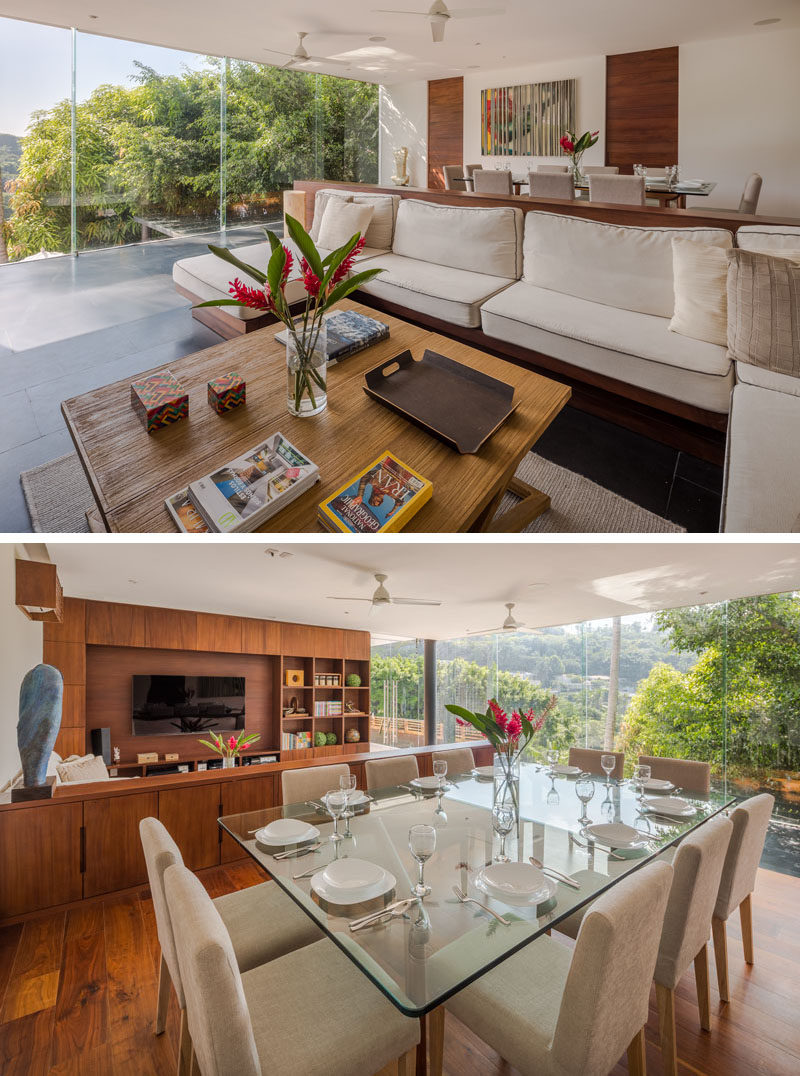 In this modern house, there's an open plan dining and living room, with the living room featuring a couch with wood cabinetry behind it. #LivingRoom #DiningRoom #Windows