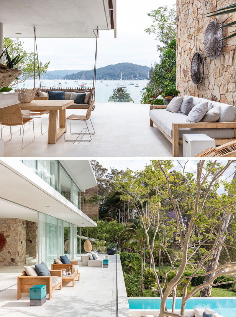This modern house has an outdoor lounge area with a ceiling-mounted swing and a large sandstone accent wall.#OutdoorSpaces #ModernHouse #SandstoneWalls