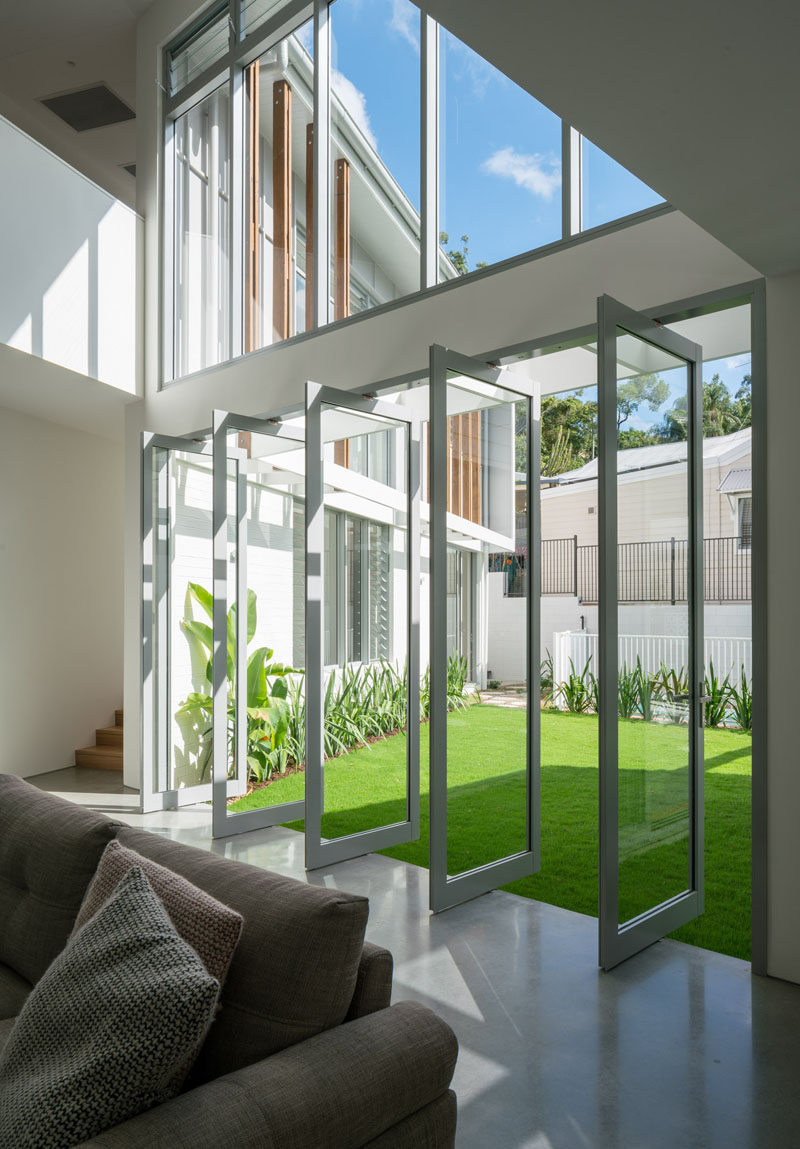 This contemporary house has pivoting glass windows that connect the courtyard and the living room. #PivotingWindows #PivotingDoors #Windows #Doors