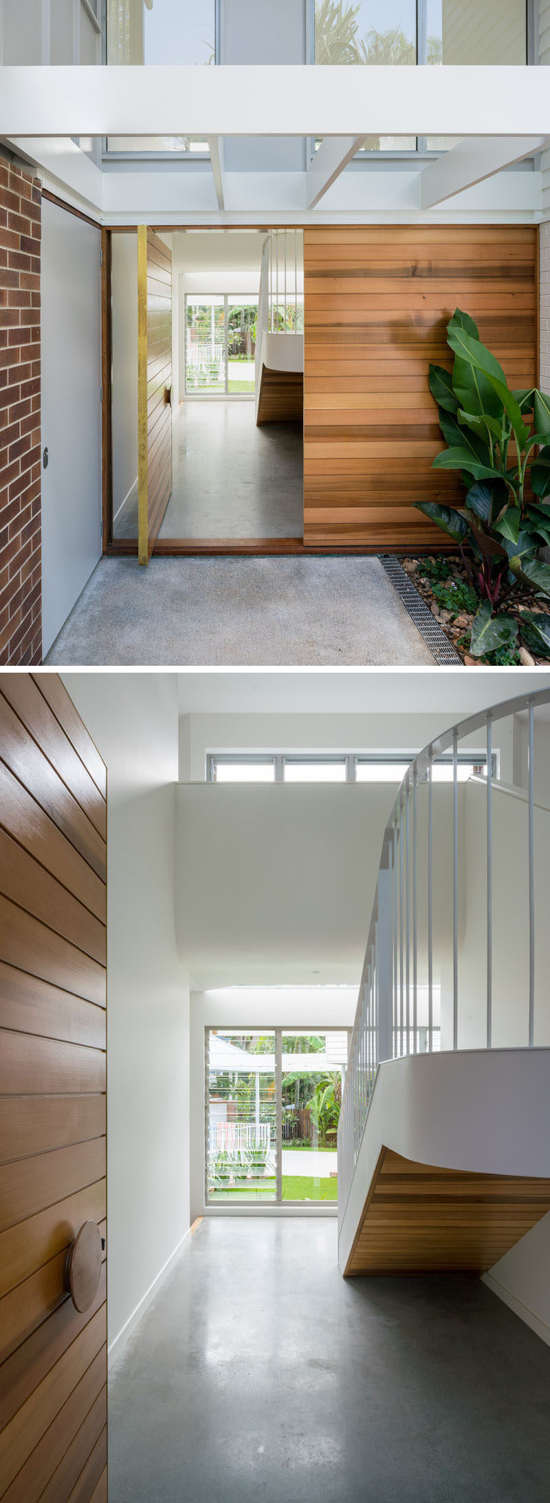 A large pivoting wood front door welcomes visitors to this contemporary home, while inside, there's the stairs leading to the upper floor, and a glimpse of the rear courtyard. #WoodFrontDoor #ModernFrontDoor #Stairs #ConcreteFloor