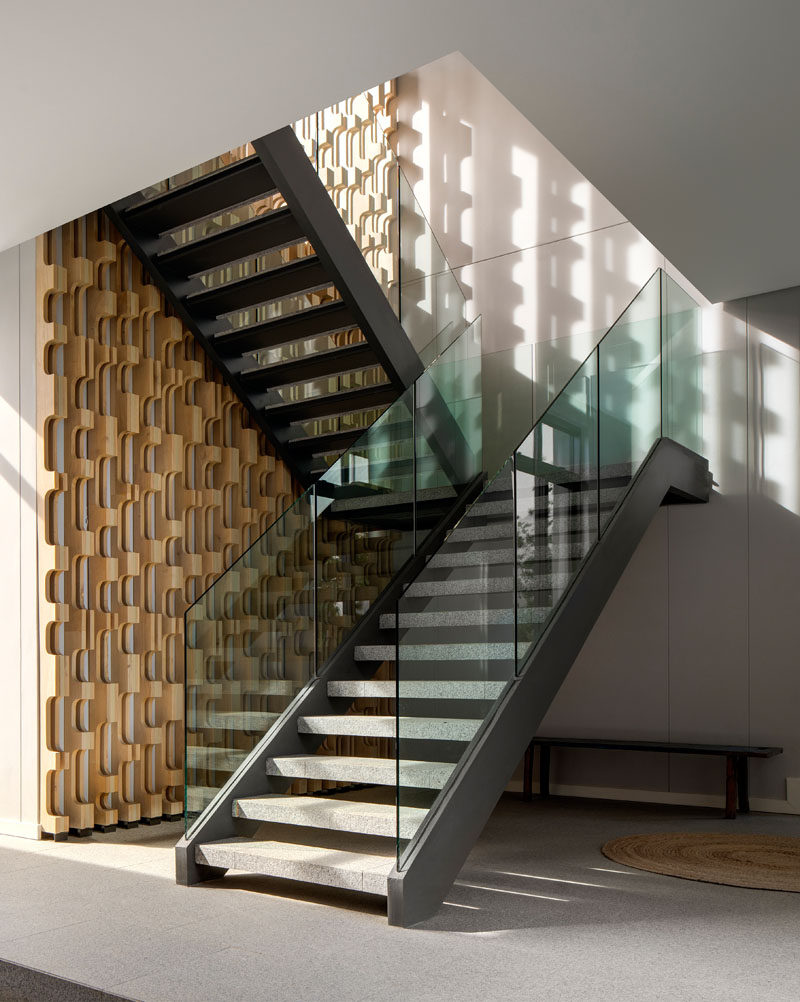 These modern stairs with a glass railing, rise alongside a CNC-cut timber screen. #CNC #TimberScreen #Stairs #ModernStairs #GlassRailing
