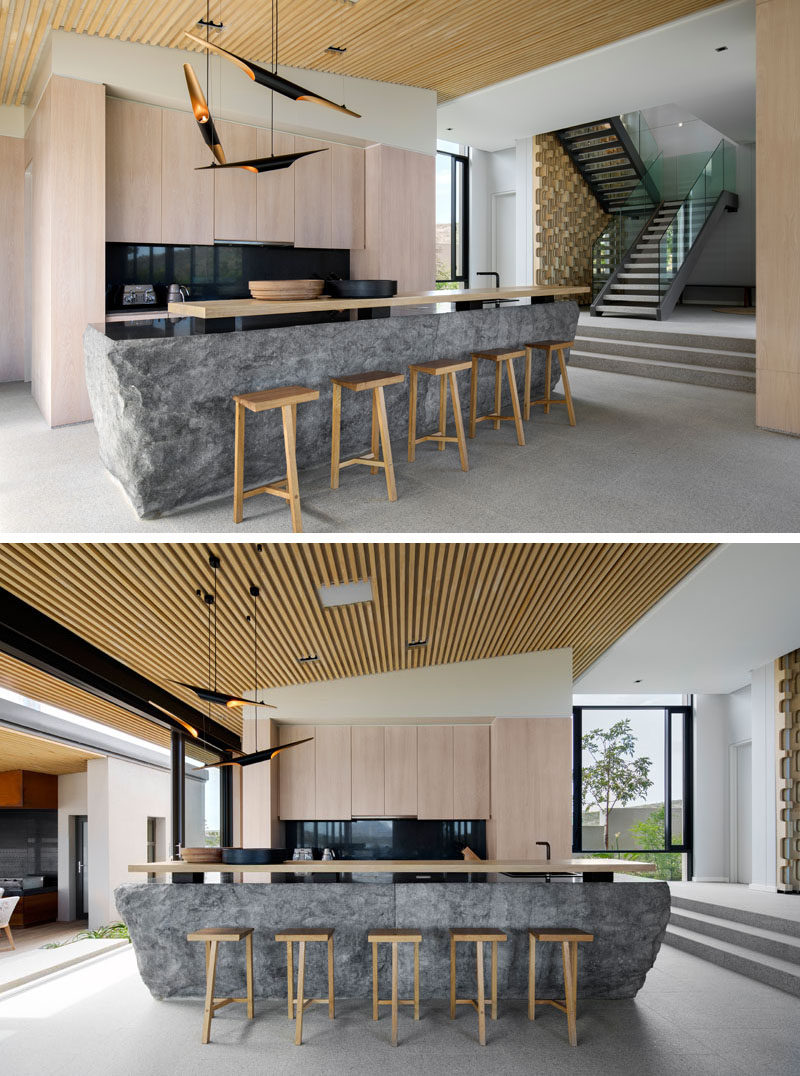 In this modern kitchen, the kitchen island has been created using rough solid blocks of granite, with a highly polished top that serves as the counter, and contrasts the light wood cabinetry and breakfast bar. #GraniteIsland #KitchenDesign #ModernKitchen #Granite