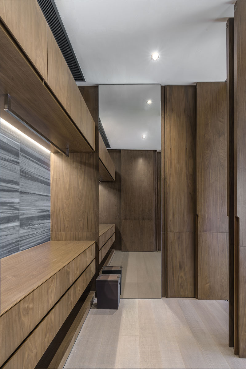 This modern walk-in closet features warm wood cabinets and a floor-to-ceiling mirror. #ModernCloset #WalkInCloset #WoodCabinets