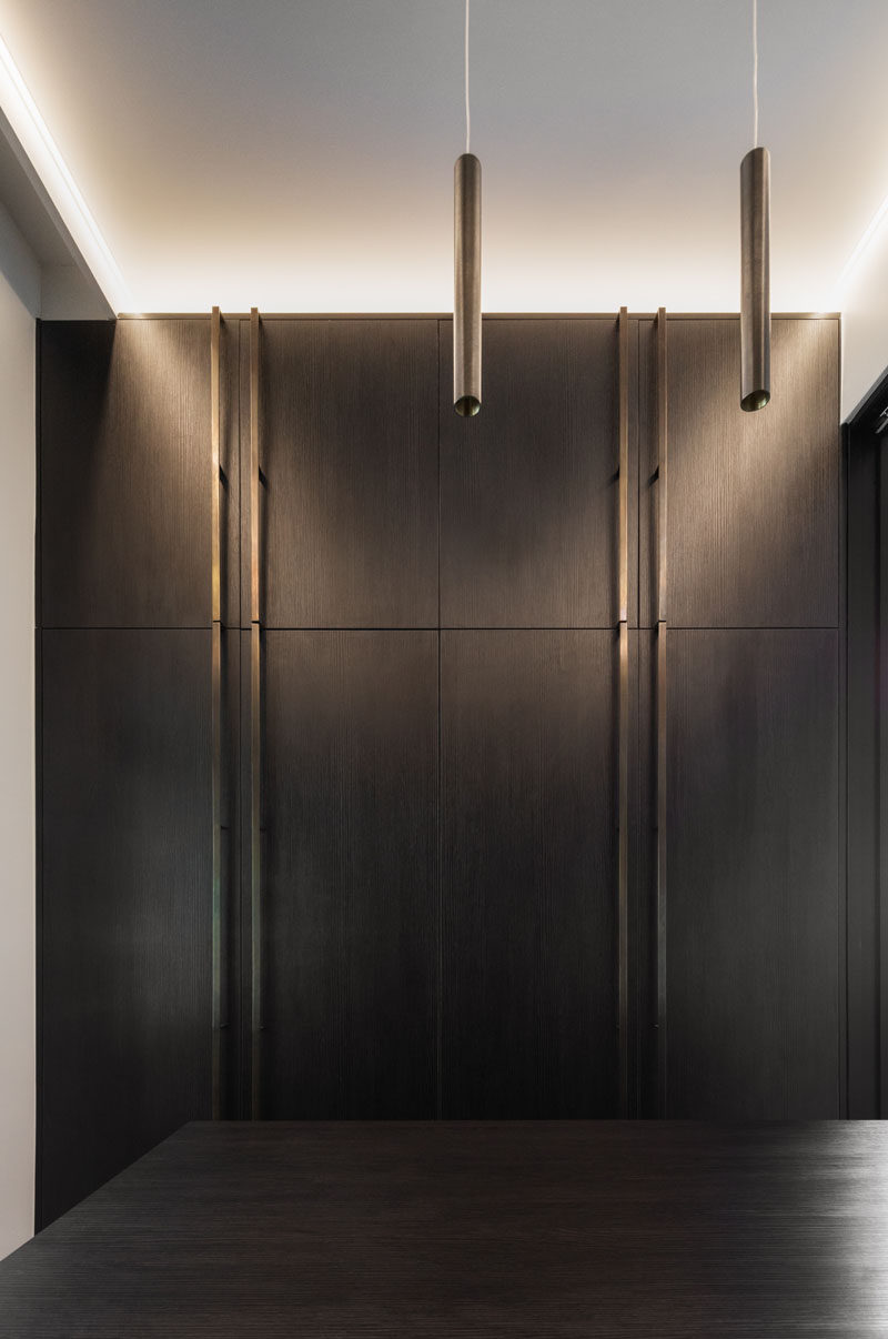 In this modern walk-in closet, dark cabinetry has been combined with bronze hardware. #DarkCabinetry #BronzeHardware #WalkInCloset