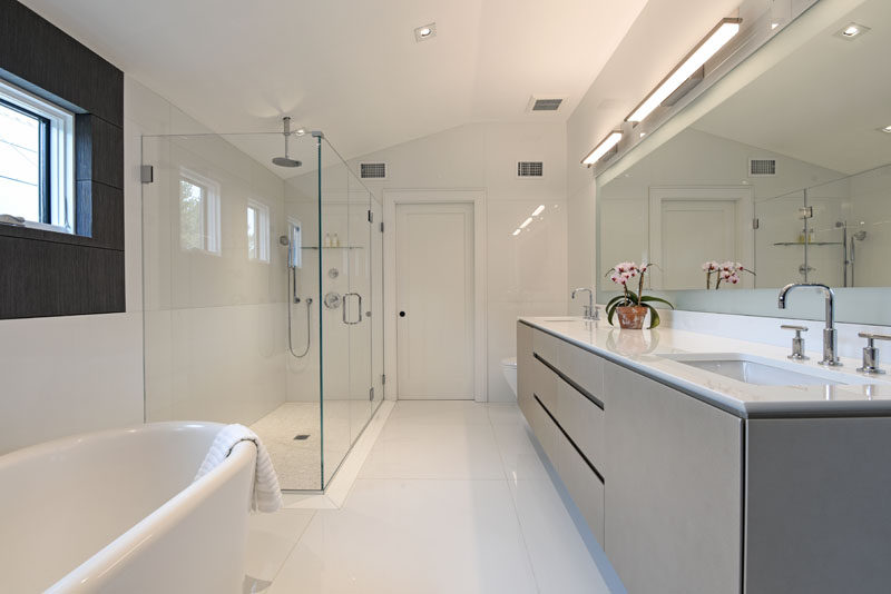 This modern bathroom features a grey vanity and white freestanding bathtub. A glass shower surround helps to keep the bathroom feeling bright and open. #ModernBathroom #GreyVanity #GreyAndWhite
