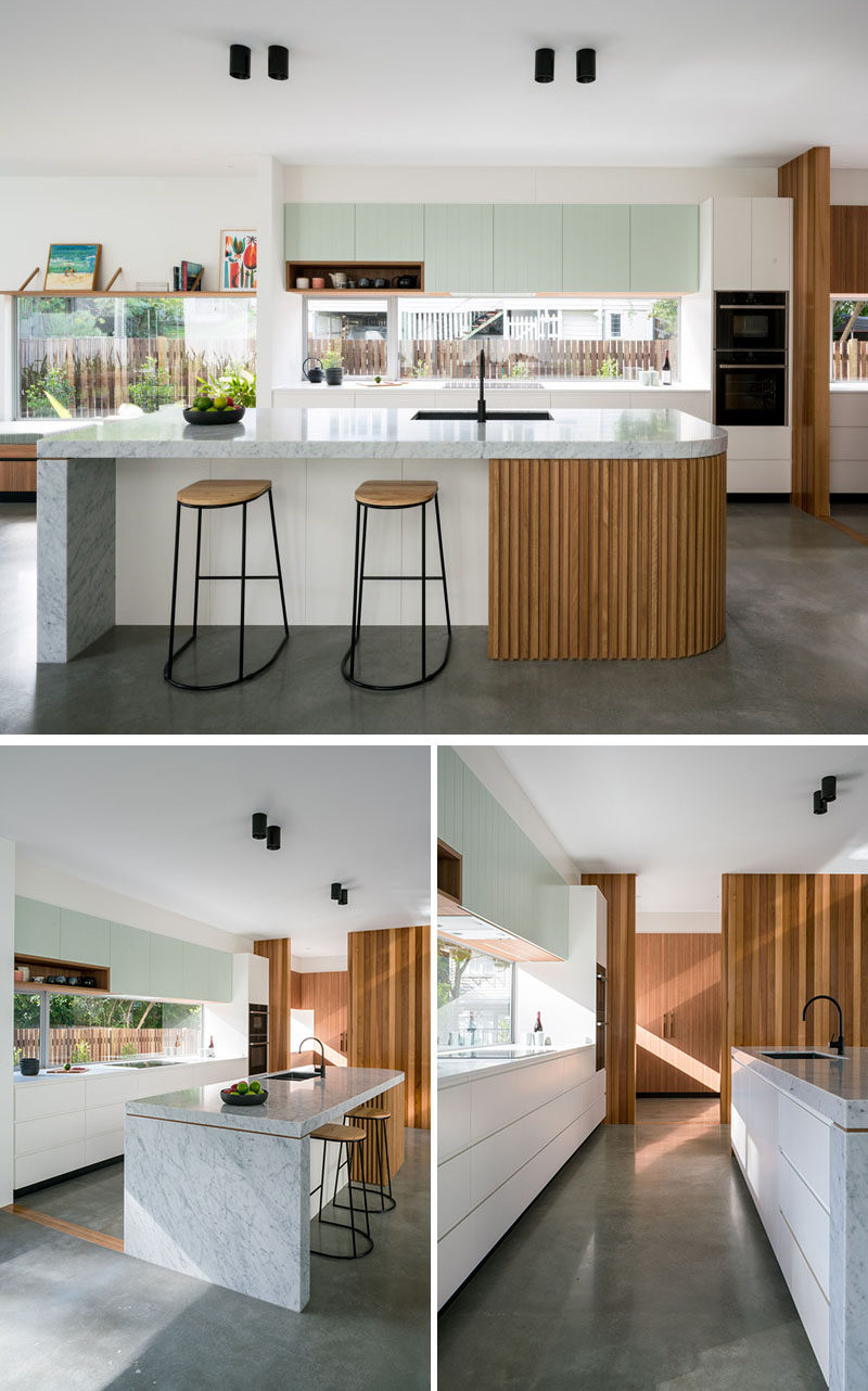 In this modern kitchen, simple and minimalist cabinets have been paired with a large island with a curved end. At the end of the kitchen is a large pantry with plenty of storage. #Kitchen #ModernKitchen #Pantry