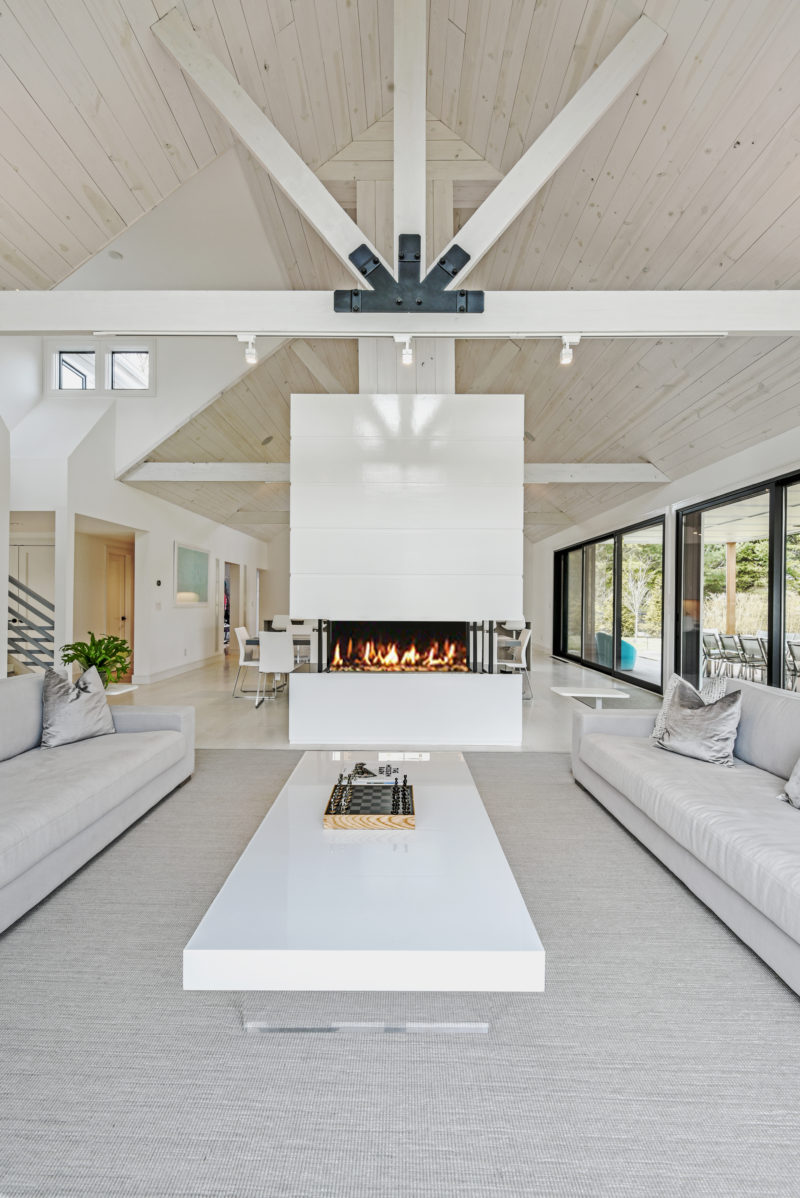 A double sided fireplace with a white surround draws the eye upwards to the exposed pitched ceiling and the structural supports of this modern barn interior. #Fireplace #ModernBarn #WhiteInterior