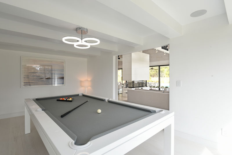 In this modern games room, there's a minimalist white pool table with a grey surface. #PoolTable #ModernGamesRoom