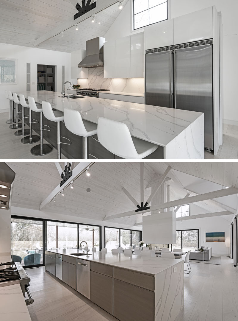 In this modern kitchen, white cabinets have been paired with wood and stainless steel elements. The long 16 foot kitchen island has enough room to seat eight people. #ModernKitchen #KitchenDesign #LongKitchenIsland
