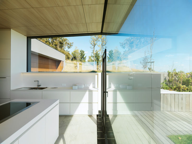This minimalist, white kitchen, features large windows for maximizing the views and the natural light. #WhiteKitchen #Windows #ModernKitchen