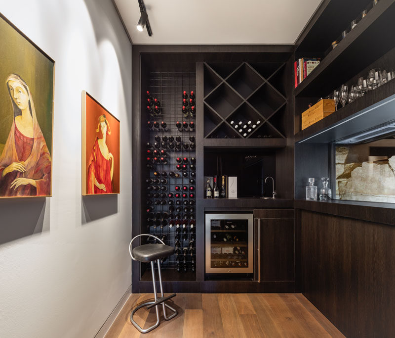 This modern wine cellar has dark custom joinery creates plenty of space for storing bottles, books and glassware. #WineCellar #WineStorage