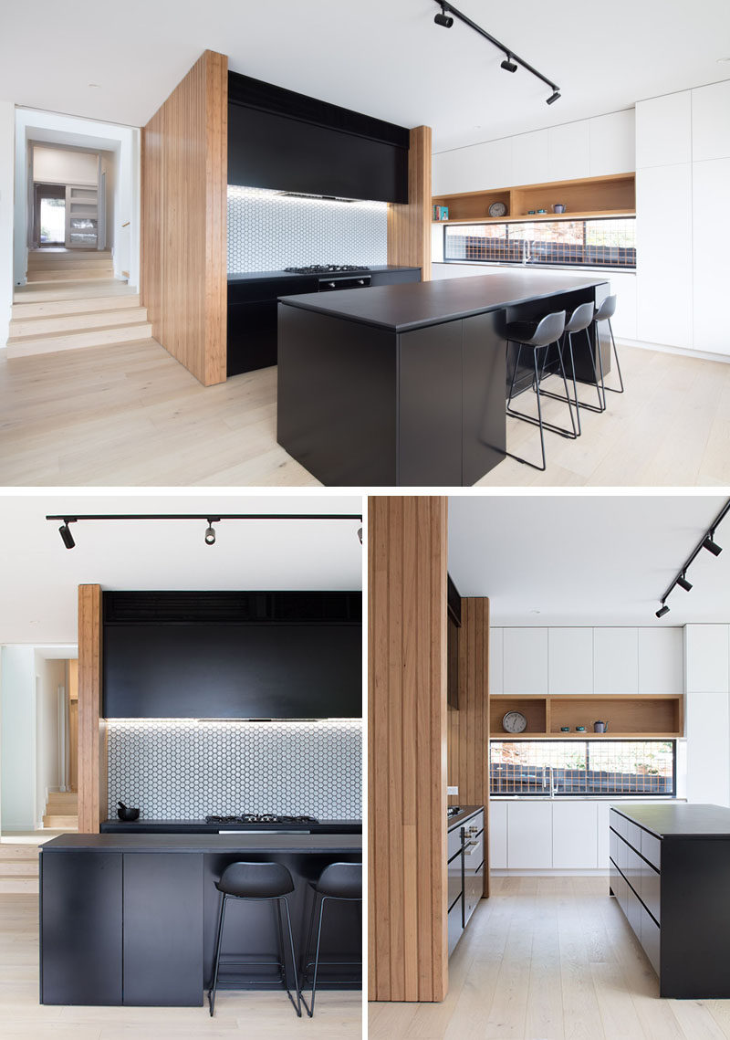 In this modern kitchen, a black island and black cabinets strongly contrast the wood elements, while white cabinets feature on the adjacent wall. #ModernKitchen #BlackKitchen #KitchenDesgin
