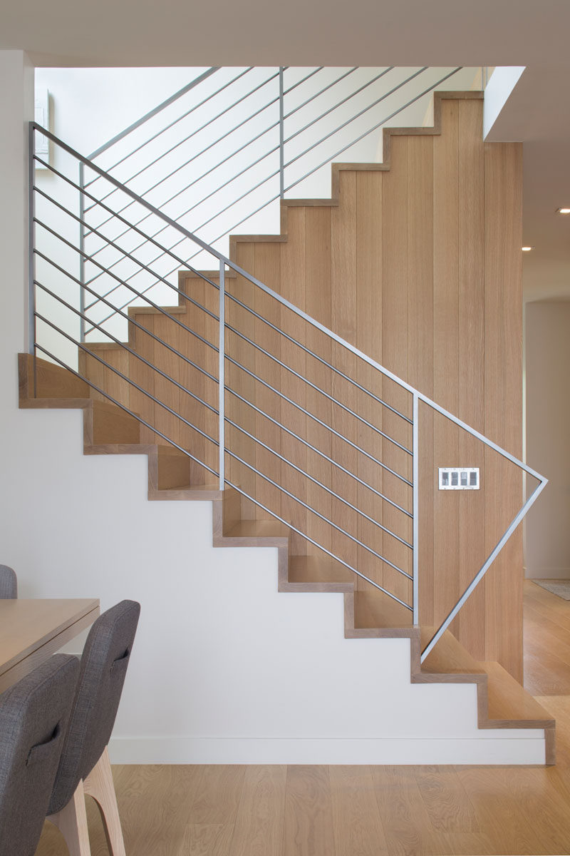 This modern house has wood stairs with a simple metal handrail that lead upstairs. #WoodStairs #Handrail #InteriorDesign