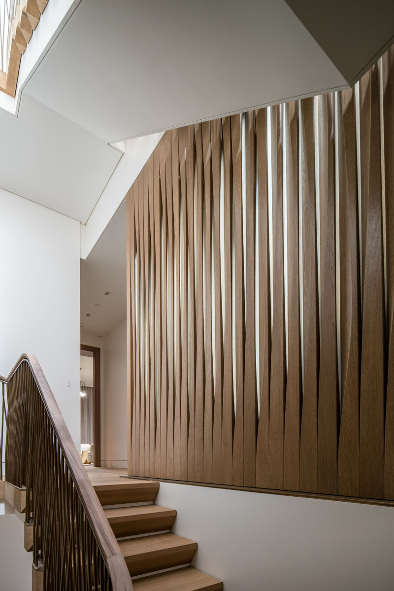 A screen of carved fumed oak and glass separates the main stairs and master dressing room in this contemporary house. #WoodScreen #Screen #ModernScreen