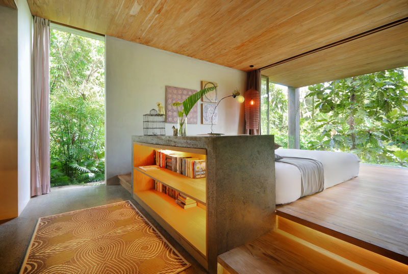 This modern bedroom that has views of the trees, has the bed raised on a wood platform. #ModernBedroom #RaisedBed