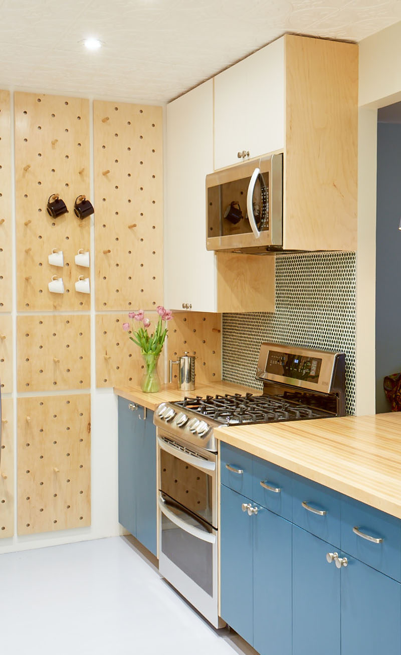 This small and modern kitchen has a custom pegboard wall, a tall curved corner shelf, and open shelves, to increase the storage the kitchen. #KitchenDesign #SmallKitchen #ModernKitchen #Pegboard