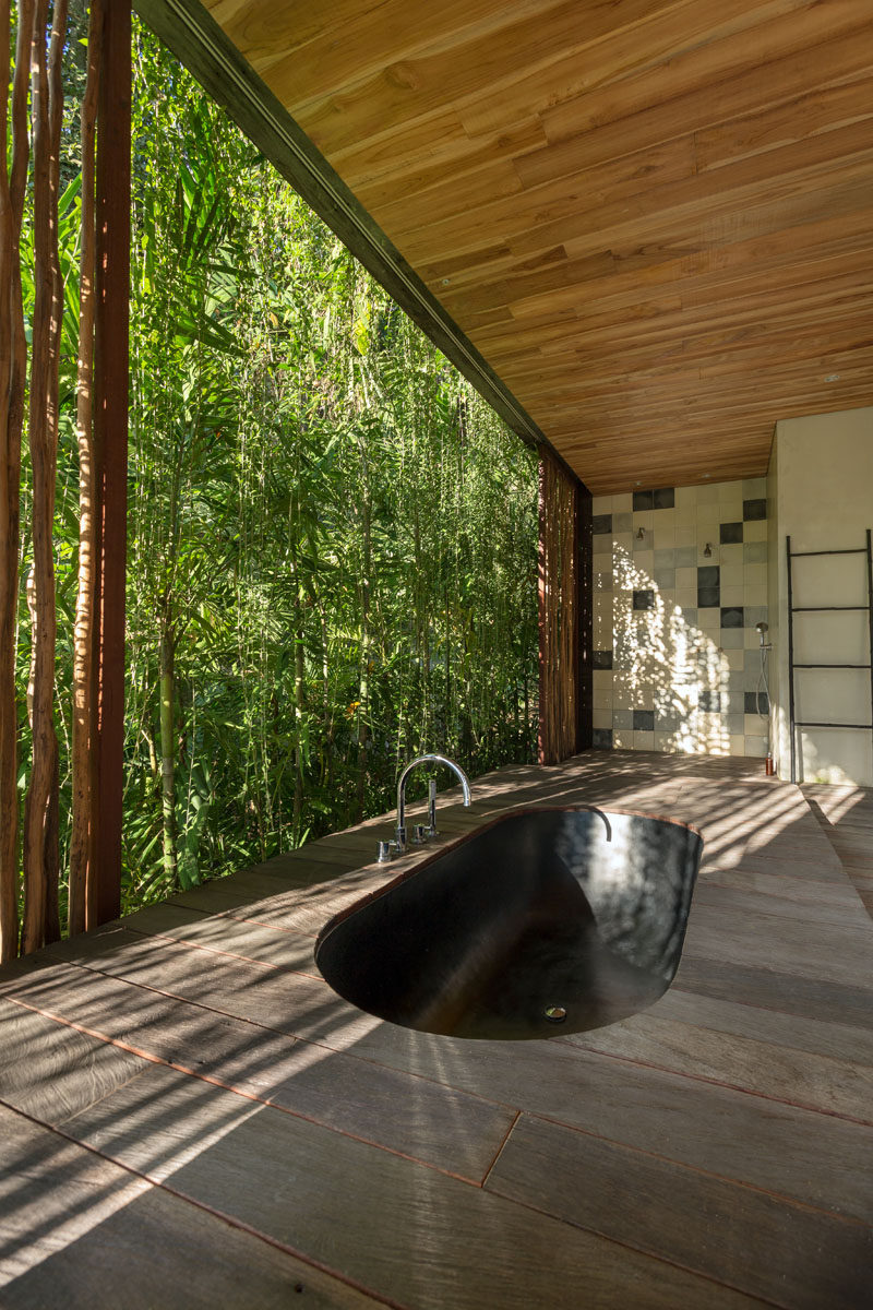 In this modern bathroom, a black sunken bathtub surrounded by wood is positioned for relaxing tropical garden views. #SunkenBathtub #BlackBathtub #TropicalBathroom #ModernBathroom