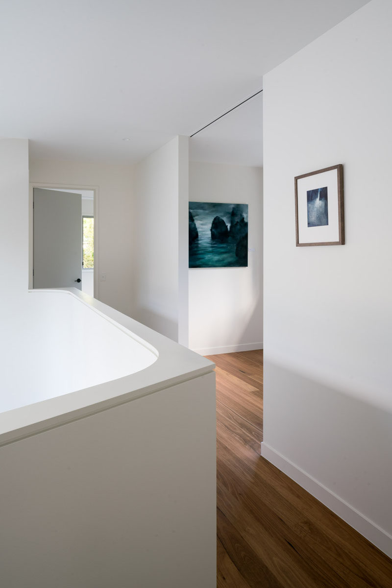 This open hallway features wood flooring and a bright white walls, creating a gallery like experience. #WhiteWalls #WoodFlooring