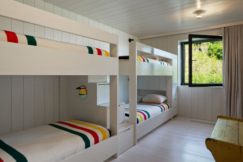 This bunkroom has been designed to run the multiple bunk beds alongside one wall, with a set of stairs with storage between them. #BunkBeds #Bunkroom #Bedroom