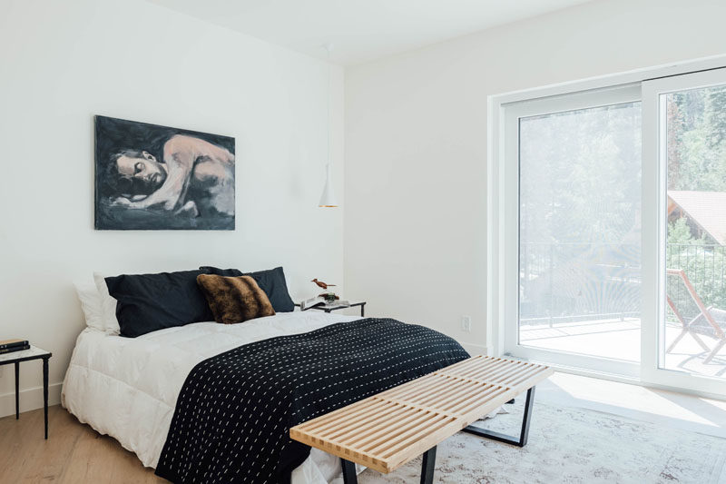 In this contemporary bedroom, the furnishings have been kept minimal, and a sliding door opens to a private deck with views of the trees. #BedroomDesign #ModernBedroom