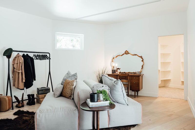 This contemporary dressing room is furnished with a couch, vanity, and freestanding clothes rack. The dressing room also has access to a walk-in closet filled with shelves. #DressingRoom #InteriorDesign