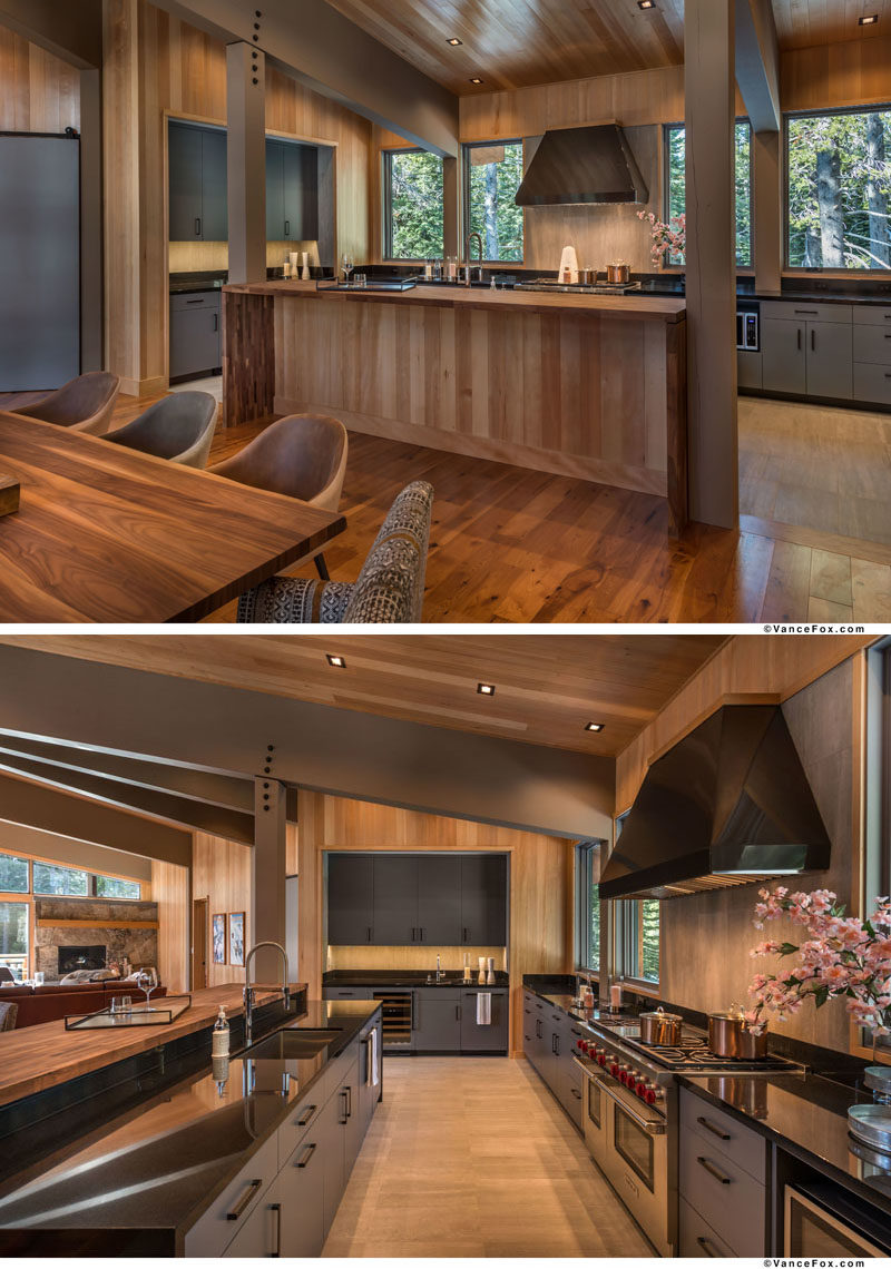 This contemporary mountain cabin kitchen features an island with waterfall slab countertops, grey cabinets, and premium appliances. #ModernKitchen #KitchenDesign
