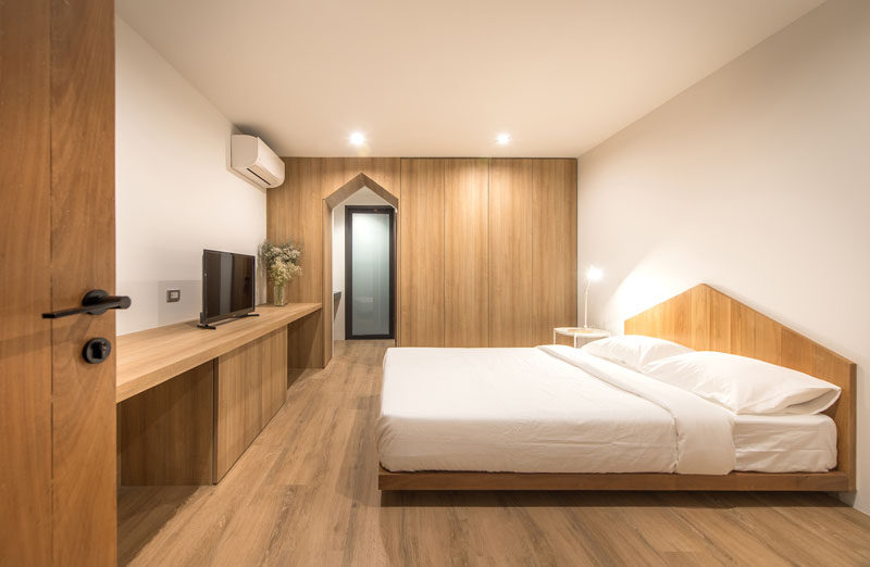 In this modern and minimalist bedroom, gabled design elements have been included in the door frame and the headboard. #Bedroom