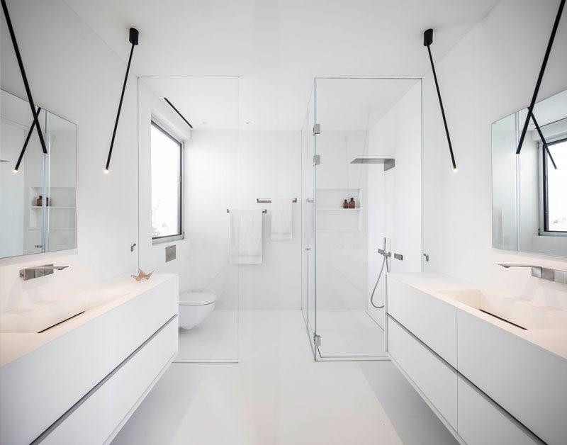 This modern master bathroom is bright white, with minimalist black lighting, and a floor-to-ceiling glass shower screen. #ModernBathroom #WhiteBathroom