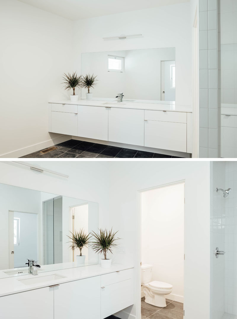 In this white bathroom, a floating vanity runs the length of the wall, and a large mirror reflects light throughout the space. #ModernBathroom #WhiteBathroom #BathroomDesign