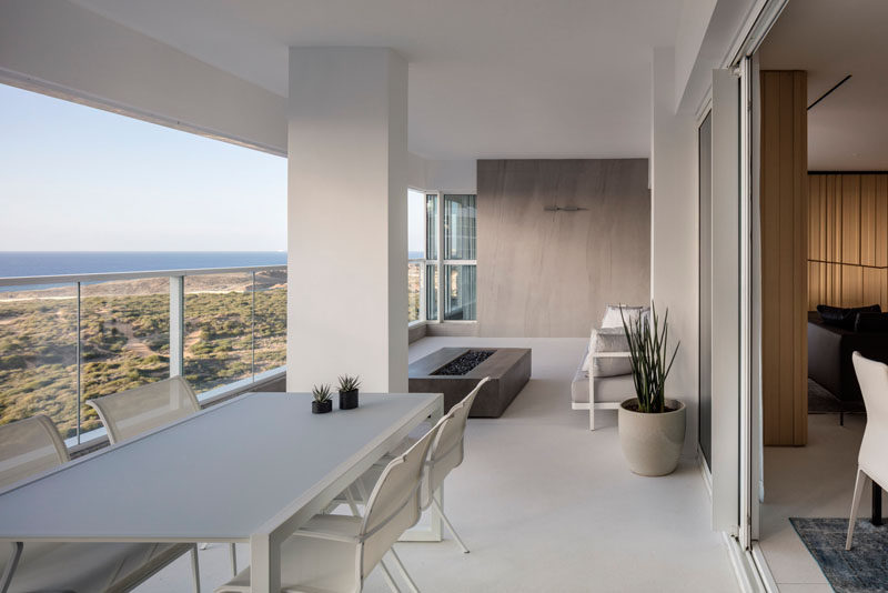This large apartment balcony has an outdoor dining area and an outdoor lounge with a freestanding fireplace. #Balcony #ModernApartment