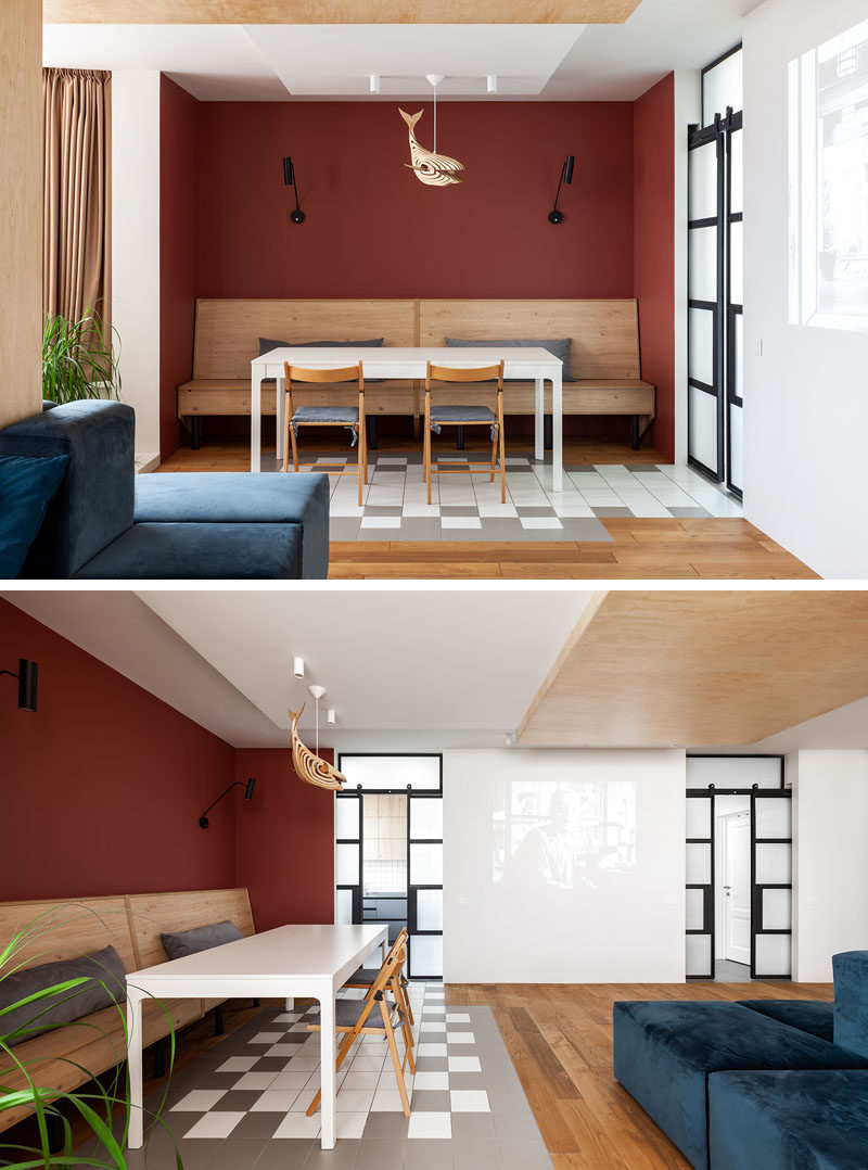 Tucked into an alcove in this modern apartment is the dining area, that's defined by deep red walls and custom design wood banquette seating. Grey and white tiles lead to the kitchen. #DiningAlcove #BanquetteSeating #DiningRoom