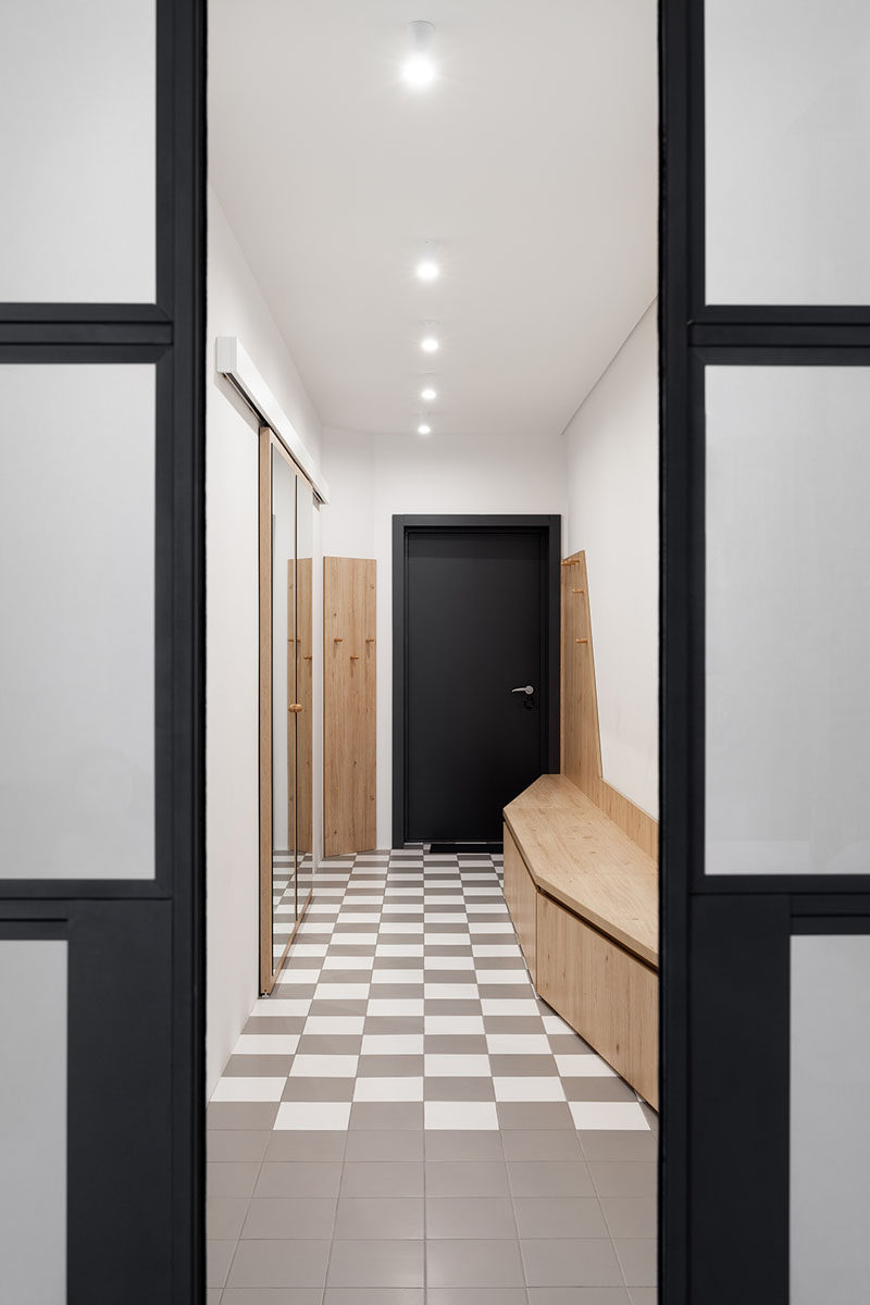 In this modern entryway, checkered tiles cover the floor, and a mirrored closet and wood bench create a place for hang coats and putting on shoes. #Entryway #InteriorDesign