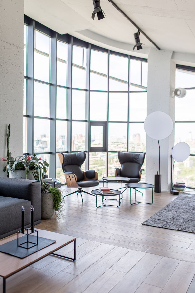 Materials like, wood, concrete, glass, and stainless steel have been used to create a industrial modern interior for this penthouse apartment. #IndustrialModern #Apartment #Windows #Penthouse