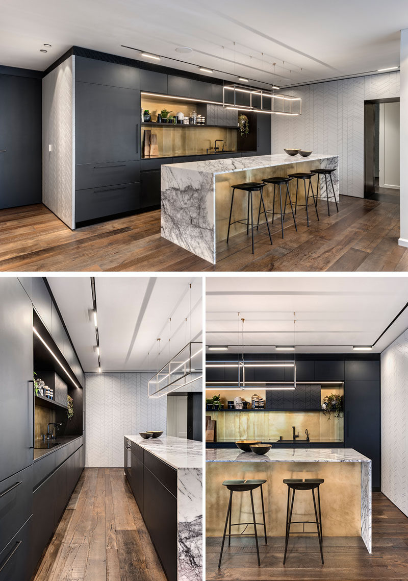 In this modern kitchen, matte black cabinets have been combined with a gold metallic backsplash and an island with a marble countertop that wraps down the sides to meet the floor. #ModernKitchen #KitchenDesign