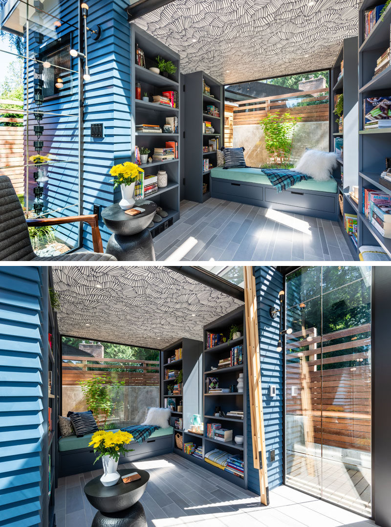 Underneath the loft bed in this modern backyard studio is an additional seating area with a built-in day bed next to a large window. The decorative wallpapered ceiling hides speakers designed to be hidden behind drywall, that are mounted in the ceiling, under the loft. #BackyardStudio #BackyardRetreat #DayBed #BuiltInBench #Bookshelves