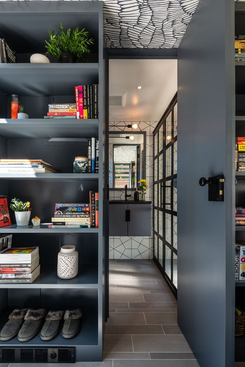 In this small backyard studio, there's a door surrounded by bookshelves that leads to a bathroom. #Bathroom #Shelving #BackyardStudio