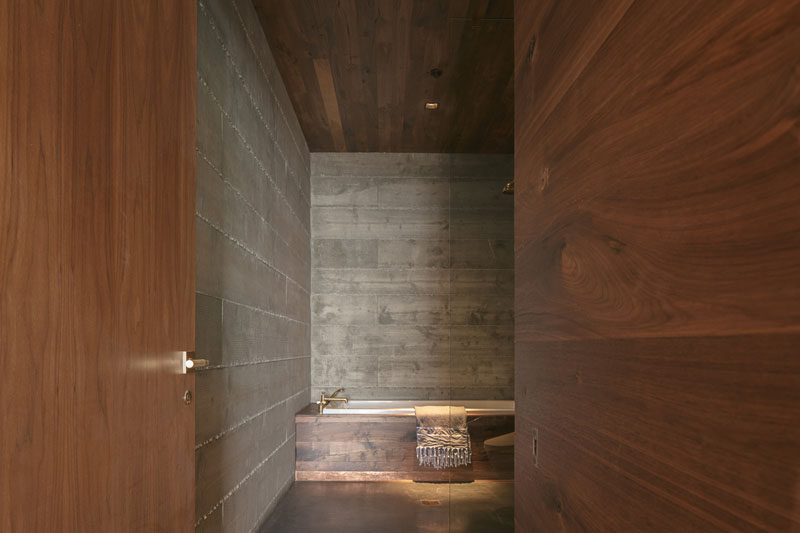 This modern bathroom has a material palette of concrete and rich walnut. #Bathroom #BathroomDesign #ModernBathroom