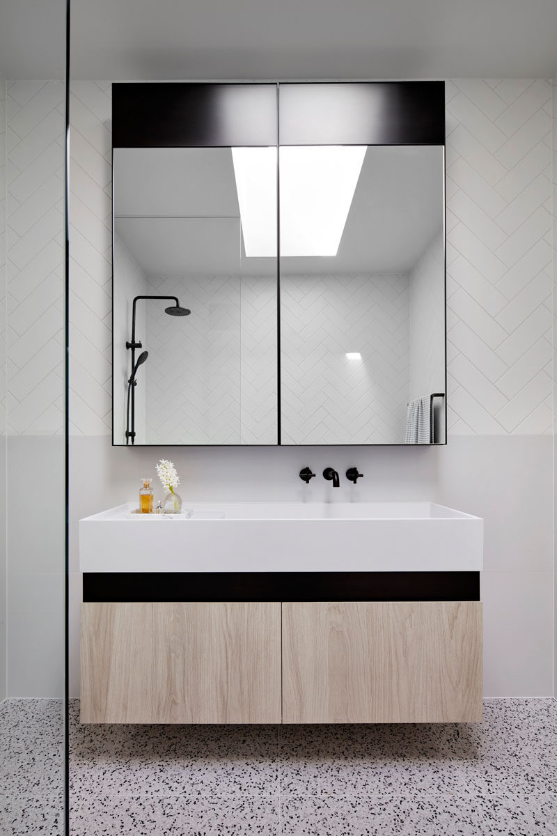 In this modern bathroom, a skylight adds natural light to the space, while the large mirror helps to reflect the light. #Bathroom #ModernBathroom #BathroomDesign