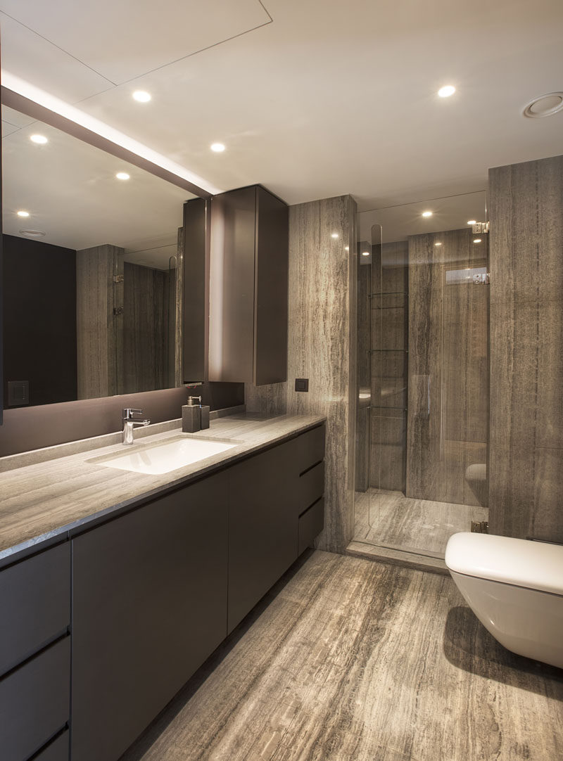 In this modern bathroom, stone covers the flooring and the shower, as well as the vanity, which has plenty of counter space and a backlit mirror. #ModernBathroom #BathroomDesign