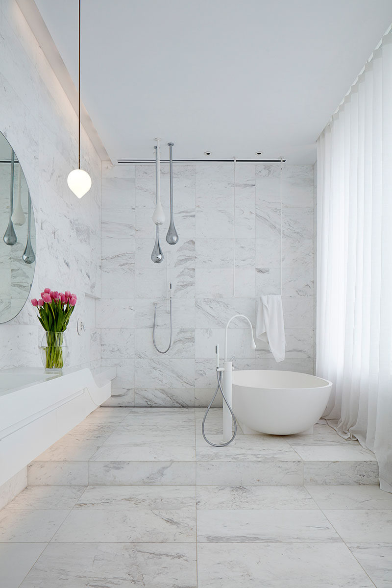 In this modern white bathroom, the walls and floor are covered in tiles, with the freestanding bathtub positioned on a raised platform. #ModernBathroom #BathroomDesign #WhiteBathroom