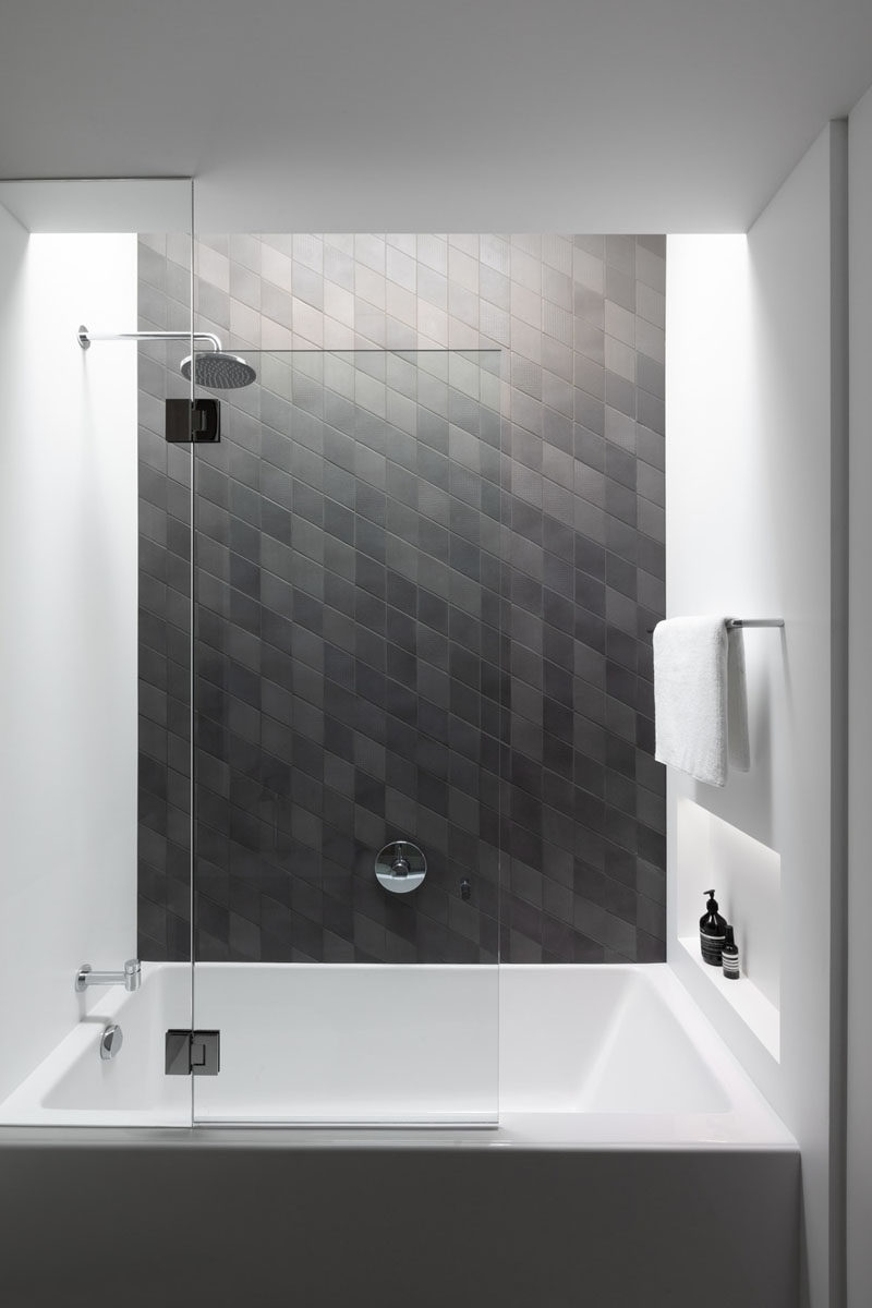 In this bathroom, dark tile has been used to create an accent wall, and a small built-in shelf with lighting at the end of the bath provides a place for storing bottles. #Bathroom #ModernBathroom #BathroomDesign
