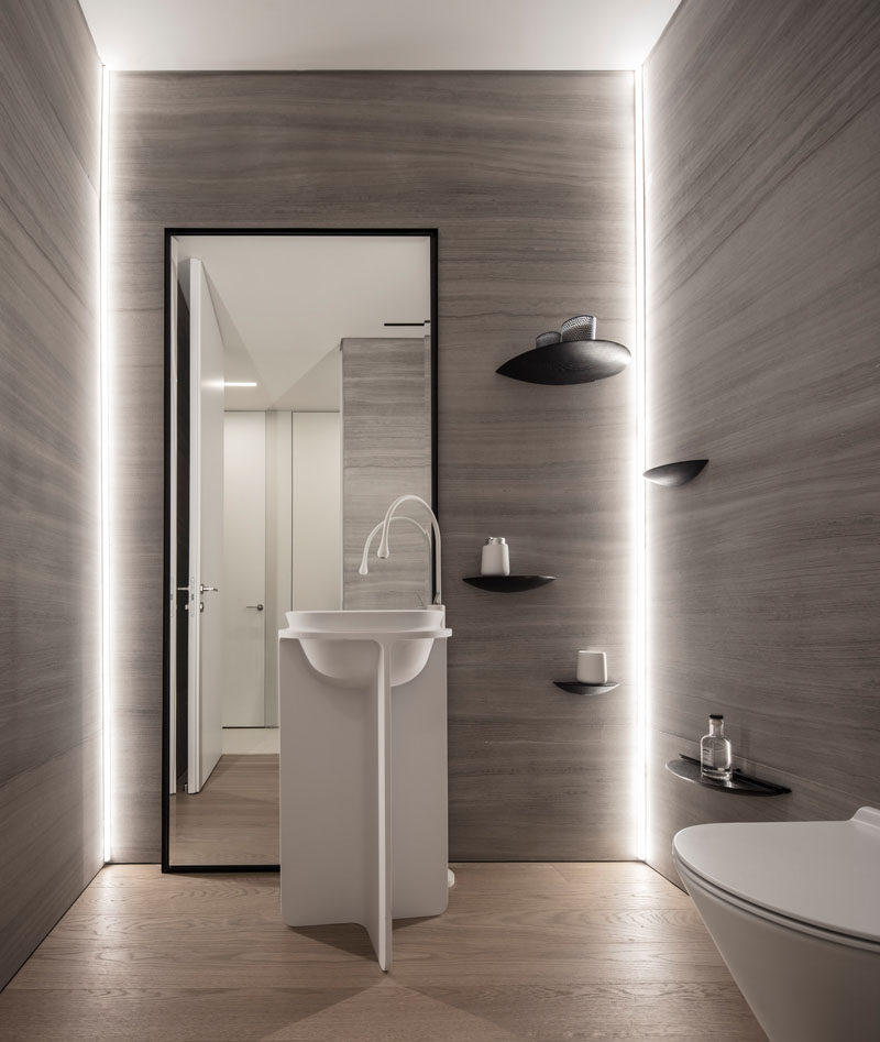 In this small bathroom, hidden lighting has been used to highlight the walls, while simple curved shelves have been mounted to the wall. #Bathroom #Lighting #Shelving #Mirror