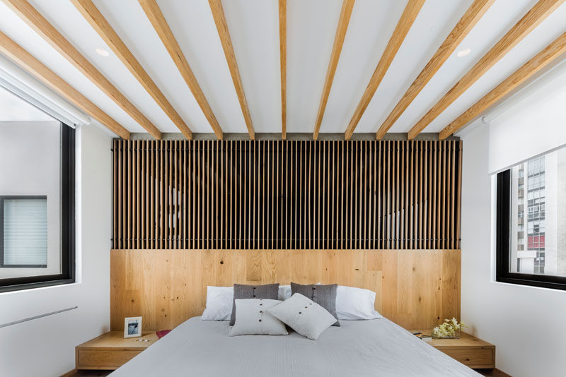 In this modern master bedroom, wood accents add warmth to the white room, while the windows on both sides allow plenty of natural light to fill the room. #Masterbedroom #BedroomDesign #WoodAccentWall