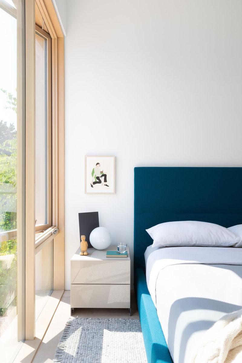 In this contemporary guest bedroom, the furnishings have been kept simple, with a blue bed frame adding some color. #GuestRoom #BedroomDesign